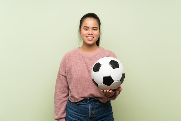 サッカーボールを保持している孤立した緑の壁の上の若い10代のアジアの女の子 Premium写真