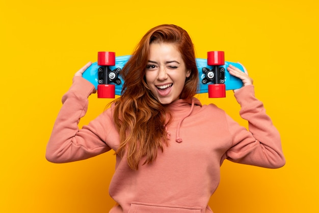 孤立した黄色の上のスケートと10代の赤毛の女の子 Premium写真