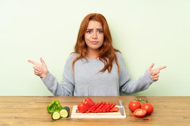 疑いを持つ側面を指しているテーブルで野菜と10代の赤毛の女の子 Premium写真