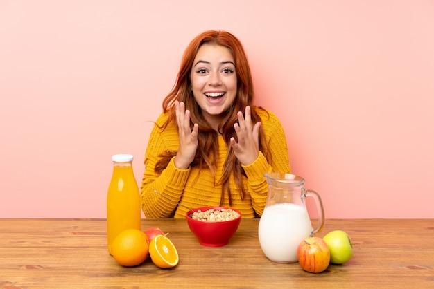 驚きの表情でテーブルで朝食を持っている10代の赤毛の女の子 Premium写真