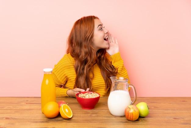 口を大きく開けて叫んでテーブルで朝食を持っている10代の赤毛の女の子 Premium写真