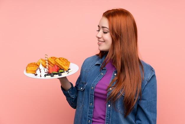 幸せな表情でワッフルを保持している赤毛の10代女性 Premium写真