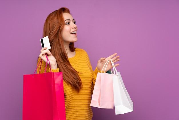 ショッピングバッグとクレジットカードを保持している赤毛の10代女性 Premium写真
