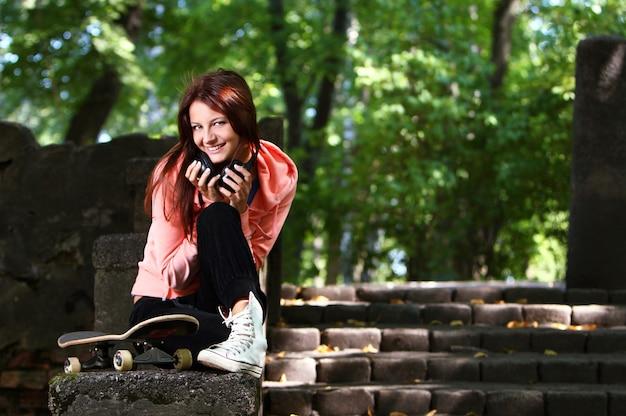 公園でヘッドフォンで美しい10代の女の子 無料写真