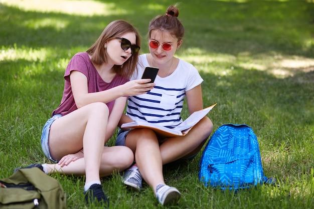 楽しい探している10代の女性はスマートフォンを保持し、友人と一緒に画面を見て、緑の芝生で休んでいる間にオンラインショッピングをする Premium写真