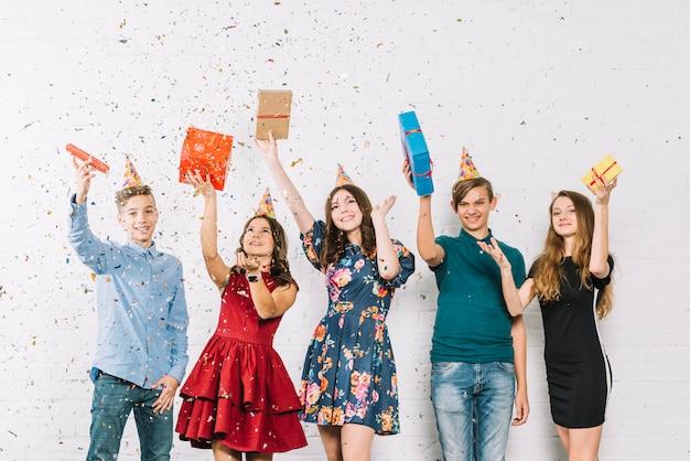 陽気な10代の友達が誕生日パーティーに紙吹雪を投げるとシャワーを浴びて 無料写真