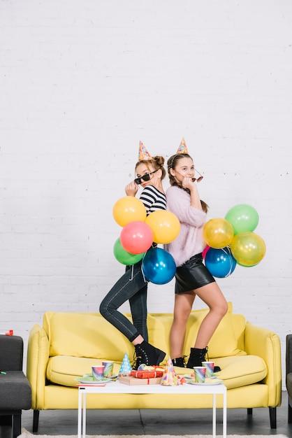 パーティーで手に風船を持って背中合わせに立っている10代の少女 無料写真