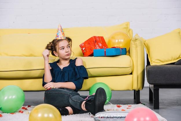 自宅の風船で白いカーペットの上に座っている怒っている10代の少女 無料写真
