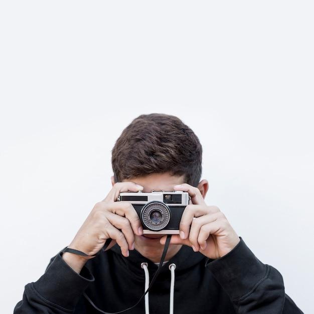 写真を撮る10代の少年のクローズアップホワイトバックグラウンドに対してレトロなビンテージ写真カメラをクリックします 無料写真