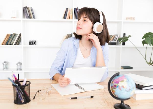 タブレットとテーブルに座っている白いヘッドフォンで10代の学生 無料写真