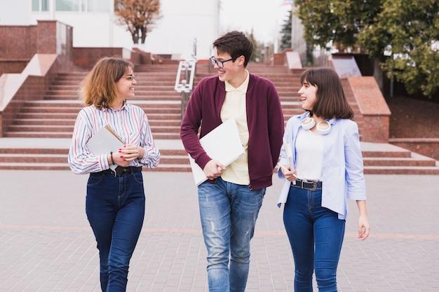 本を歩いてレッスンについて話す10代の学生 無料写真