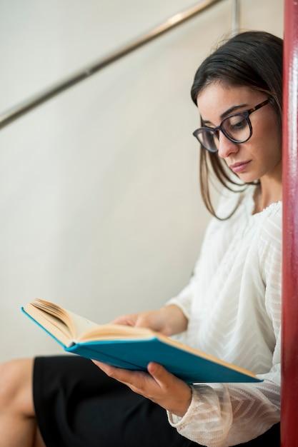 10代の女性が図書館の階段の上に座って本を読んで 無料写真
