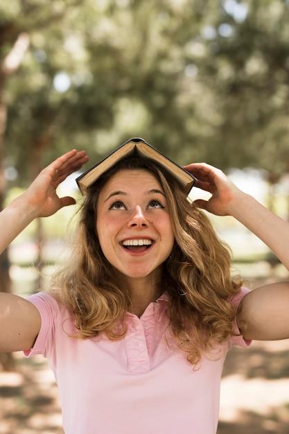 10代の学生の頭の上の本のバランスをとる 無料写真