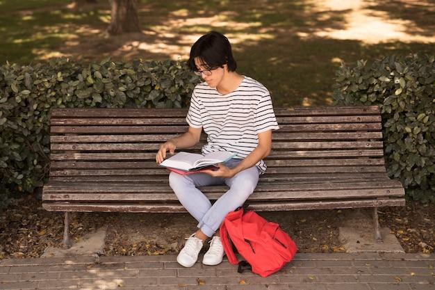 アジアの10代の男がベンチの教科書 無料写真