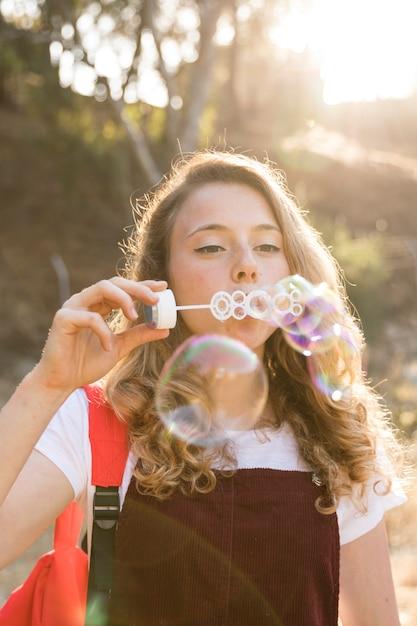 幸せな10代の公園でシャボン玉を吹く 無料写真