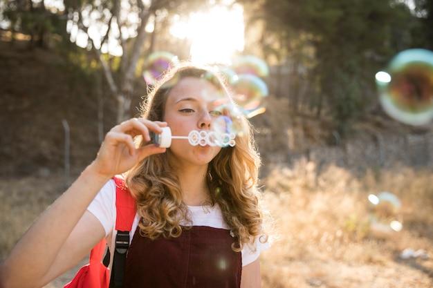 陽気な10代の自然の中の泡と遊ぶ 無料写真