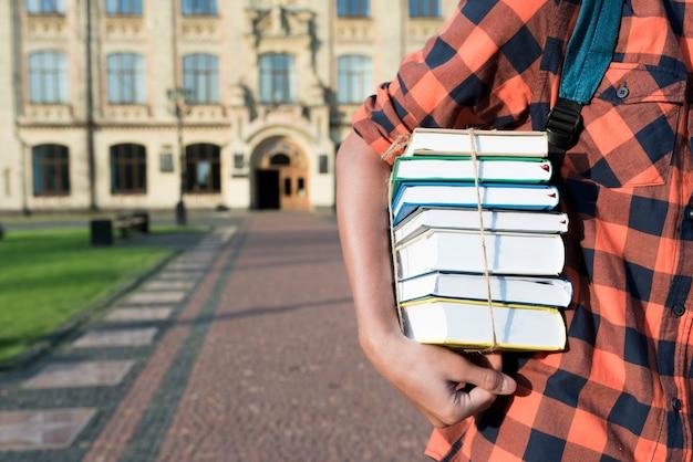 彼の腕の下で本を持っている10代の少年のクローズアップ 無料写真