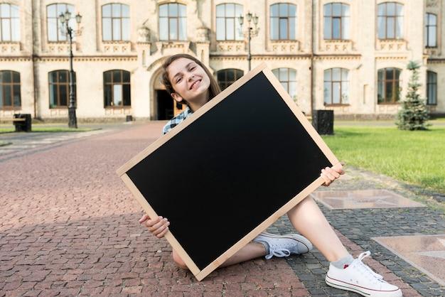 黒板を保持している正面10代の少女 無料写真