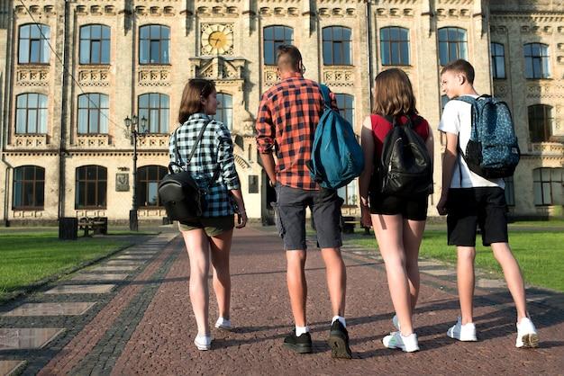 高校へ行く10代の友達の背面図 無料写真