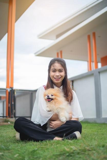 肖像画のイメージ、アジアの女性の家でポメラニアン犬と遊ぶ10代女性 Premium写真