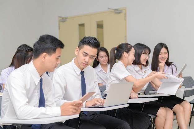 教室でノートパソコンで作業する制服を着た10代の学生 Premium写真