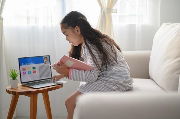 宿題を書いて、テーブルに座っている女子学生。ラップトップコンピューターを使用して勉強する10代。新しい正常。社会的距離。家にいる。 Premium写真