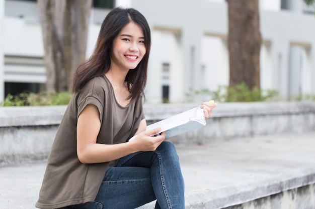 本の幸せと笑顔を読んでいるアジアの10代女性は大学で教育を楽しんでいます Premium写真