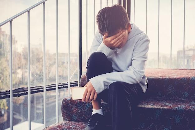 若いアジアプレティーン10代少年彼の膝を抱いて、彼の顔をカバーし、携帯電話を保持している、子供のいじめ、落ち込んでいる子供の精神的健康 Premium写真