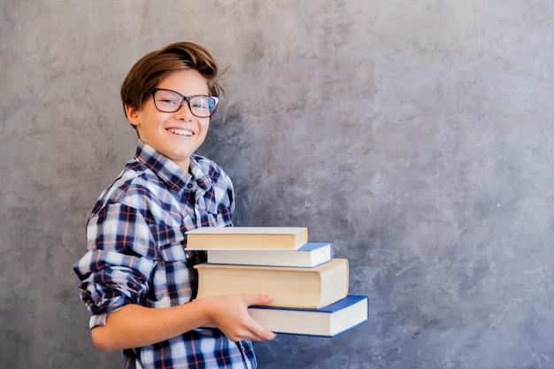 本を保持しているかわいい10代の学校の少年 Premium写真