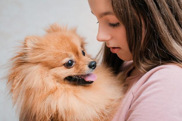 犬の品種スピッツと10代の少女は、床にペットを自宅で喜ぶ。 Premium写真