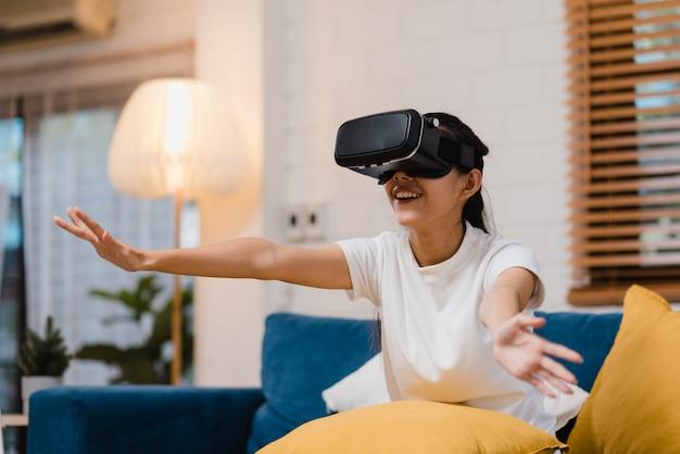 アジアの10代女性リビングルームでビデオゲームをプレイする仮想現実シミュレータを眼鏡を使用して 無料写真
