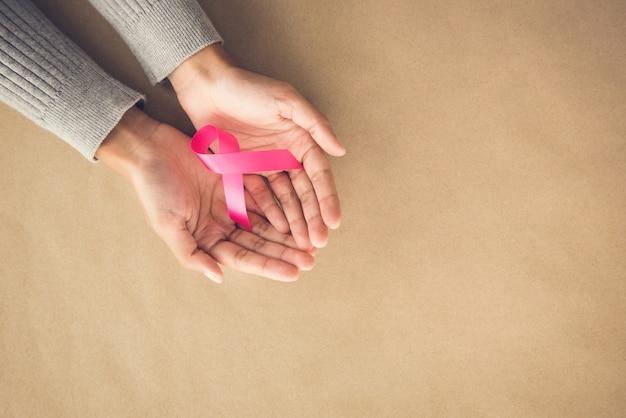 10月にサテンピンクリボンキャンペーンを与える女性の手、 Premium写真