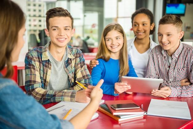 カフェのテーブルに座っている10代の若者のグループ。 Premium写真