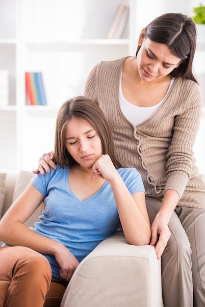 自宅でソファの上のけんかの後に母と10代の娘。 Premium写真
