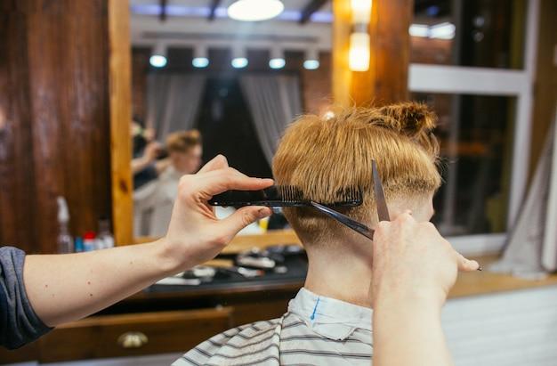 理髪店で10代の赤毛の少年散髪美容院。おしゃれな Premium写真