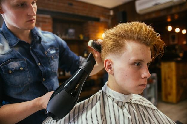 理髪店で10代の赤毛の少年散髪美容院。おしゃれでスタイリッシュなレトロな髪型 Premium写真