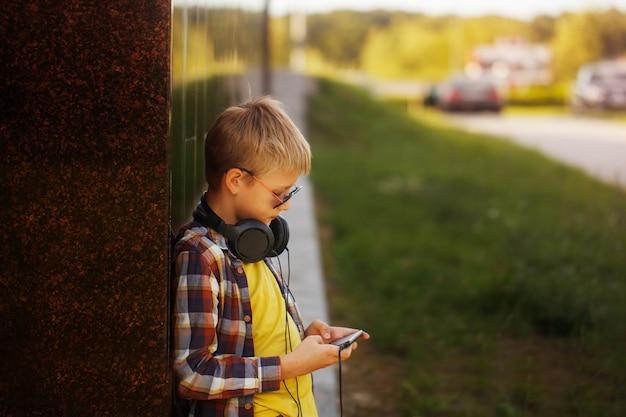 ハンサムな10代の少年が音楽を聴くと電話を使用して Premium写真