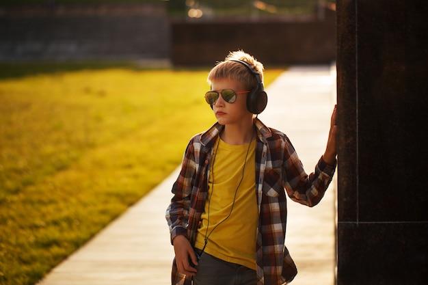 ハンサムな10代の少年が音楽を聴くと日没に携帯電話を使用して Premium写真