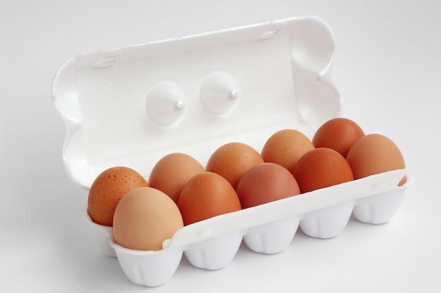 白い発泡スチロールの白い背景の上の10の鶏の茶色の卵。分離しません。 Premium写真