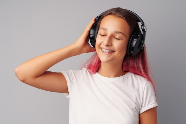 彼女のヘッドフォンで音楽を聴く若い女の子10代 Premium写真