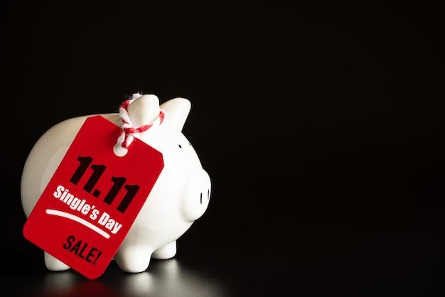 オンラインショッピング一日の販売の概念。赤いチケット11.11の販売タグは、ピギーバンクでぶら下がっている Premium写真