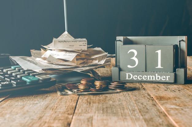 木製のテーブルに手形電卓お金。 12月31日 Premium写真