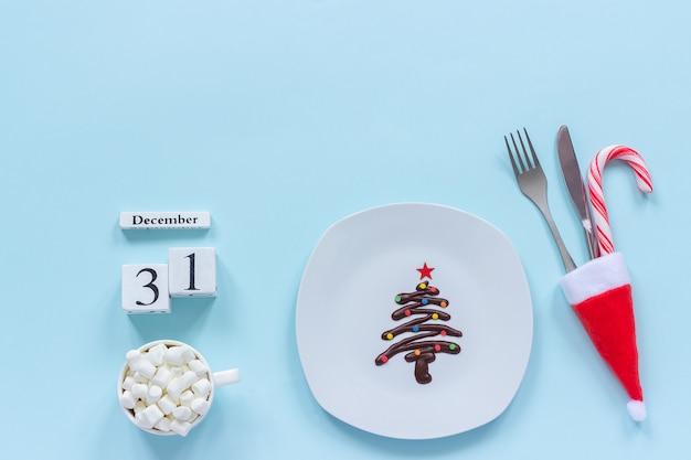 カレンダー12月31日。プレート、カトラリー、ココアのカップに甘いチョコレートクリスマスツリー Premium写真