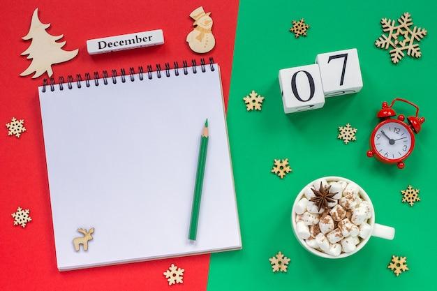 カレンダー12月7日カップココアとマシュマロ、空の開いたメモ帳 Premium写真