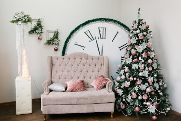 クリスマスと新年の装飾。クリスマスツリー、ソファ、12時を示す大きな時計 Premium写真