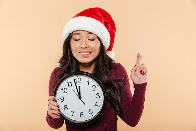 Портрет мечтающей девушки в красной шапке санта-клауса, держащей часы, показывающие почти 12 загадывающих желание пальцами на фоне персика Бесплатные Фотографии
