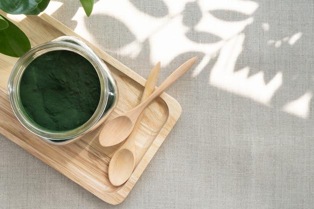 Крупный план микроскопических сине-зеленых водорослей - порошка спирулины в стеклянной банке. это отличная биологически активная добавка для веганской, вегетарианской или растительной диеты, поскольку она содержит поливитамины и содержит в12. Premium Фотографии