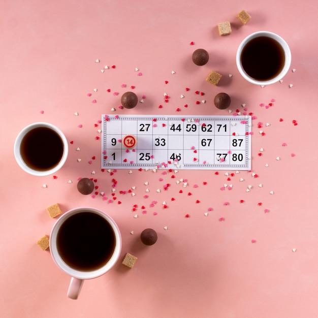 Лото билет с деревянной бочкой 14 номер и чашки кофе, конфеты конфеты шоколад на фоне розового сердца. день святого валентина 14 февраля минимальная концепция. квадратный формат Premium Фотографии