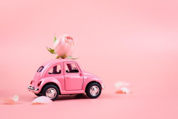 Розовый ретро игрушечный автомобиль поставляет розовый цветок на розовом фоне. открытка 14 февраля, день святого валентина. 8 марта, международный женский день Premium Фотографии