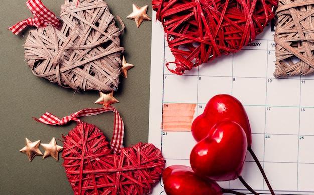 2月14日、クラフト赤いハートの背景、バレンタインデーのカレンダー Premium写真
